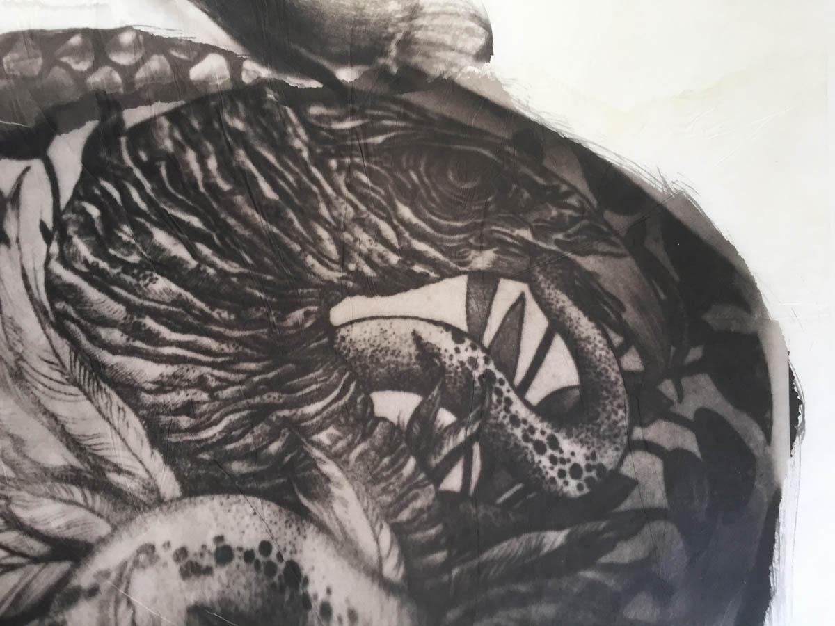 A close-up of a bird and snake tattoo.
